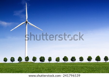 Wind Turbine on front of a green wheat field and line of trees - stock photo