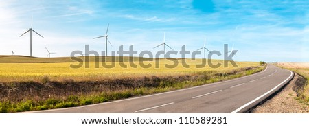 Wind turbine on green and yellow field. Empty road in foreground, blue sky with clouds in background. Alternative energy source, production and power generation. Ecology and freedom concept. Panorama. - stock photo