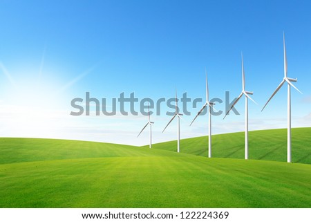 Wind turbine on green grass field - stock photo