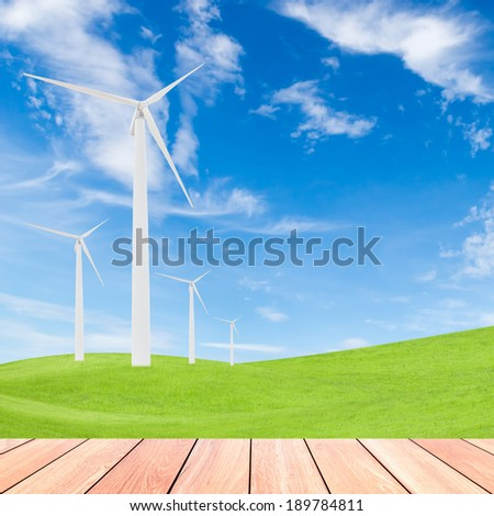 wind turbine on green grass field and blue sky background with wood plank foreground,used for green earth concept