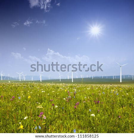 Wind turbine on the green grass over the blue clouded sky - stock photo