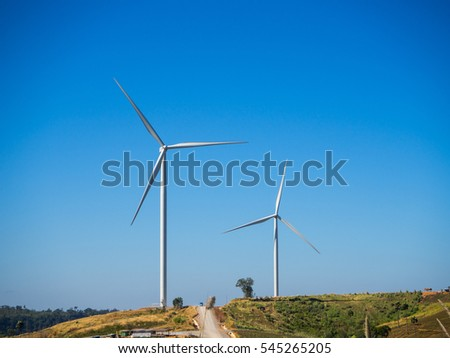 wind turbine on the green grass over the blue sky