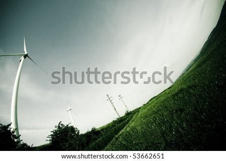 Wind turbine on the meadow shown by fisheye lens - stock photo