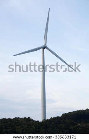 Wind turbine on top of mountain, against blue sunny sky background.