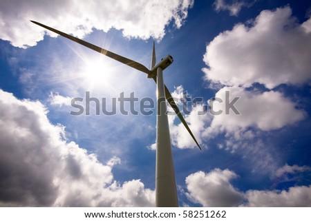 Wind turbine over a cloud filled blue sky, alternative energy source - stock photo