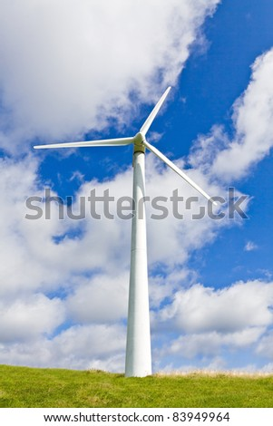 Wind turbine over blue sky on green meadow