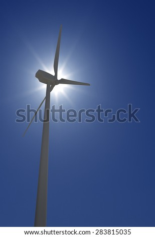 Wind Turbine over sun shine and clear blue sky - stock photo