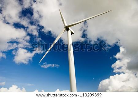 Wind turbine over the deep blue clouded sky - stock photo