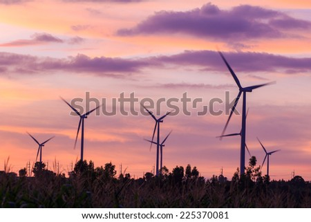 Wind turbine power generator at twilight sunset - stock photo