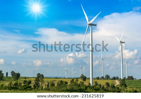 Wind turbine power generator on blue sky - stock photo