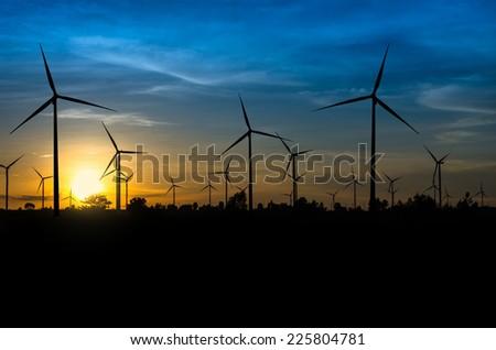 Wind turbine power generator with sunset - stock photo