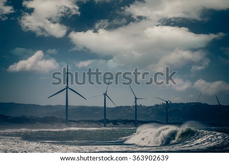 Wind turbine power generators silhouettes at ocean coastline at sunset. Alternative renewable energy production in Philippines - stock photo