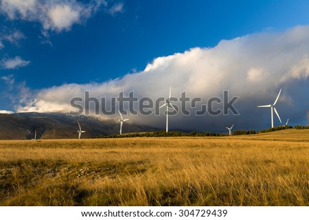 Wind turbine power plant located over a valley. Used for producing green energy from the wind.