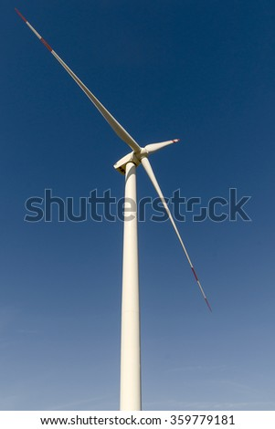 Wind turbine producing alternative energy on blue sky