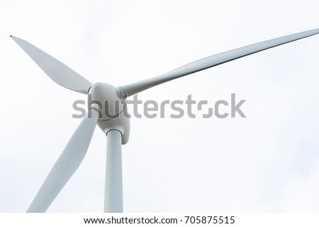 Wind turbine propeller on cloudy sky background.