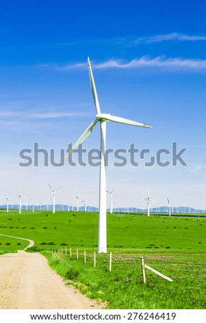 wind turbine,road and meadow under blue sky - stock photo
