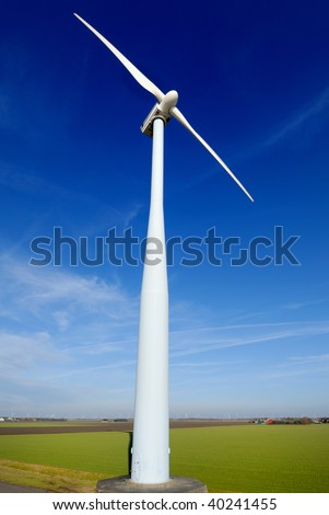 Wind turbine seen from a low point of view, which stand on a flat meadow against a blue sky. On the horizon more windmills can be seen.