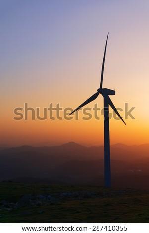 wind turbine silhouette on mountain at sunset - stock photo