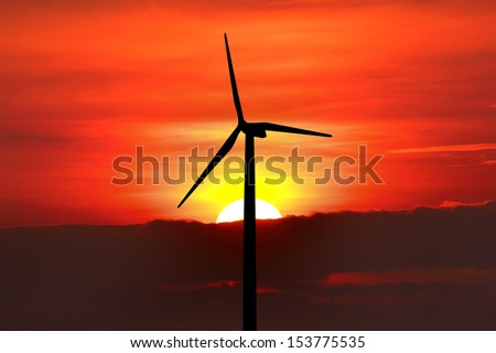Wind turbine silhouette on sunset background - stock photo