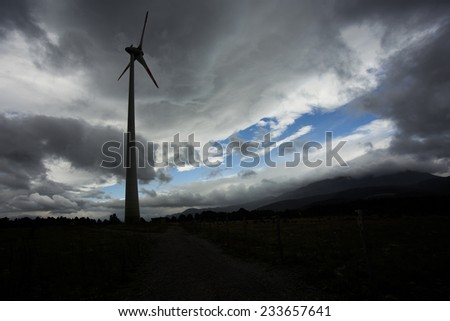 Wind turbine silhouette, with dark landscape background. - stock photo