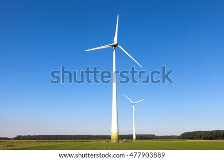 Wind turbine spinning with in a green countryside environment