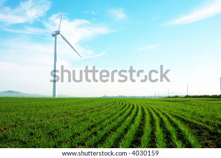 Wind turbine standing against a blue sky with some clouds in a green grass field - stock photo