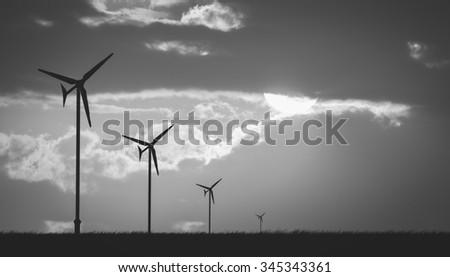 wind turbine sunset background ecosystem , black and white - stock photo