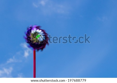 Wind turbine toy on blue sky - stock photo