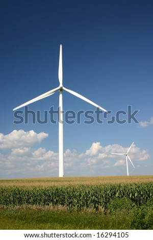 Wind turbine turning in a cornfield on a sunny day, with motion blur on blade tips.