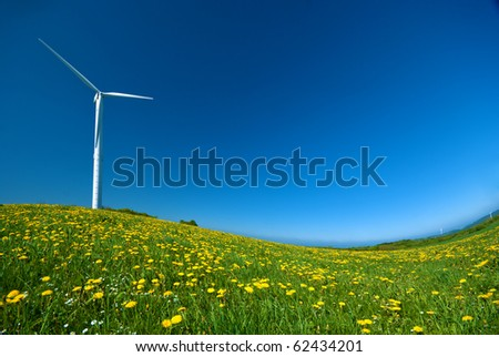 Wind turbine under blue sky - stock photo