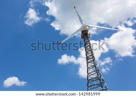 Wind turbine with blue sky and white cloud