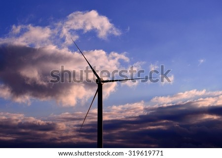 Wind turbine  with clouds background and blue sky at dawn  - stock photo