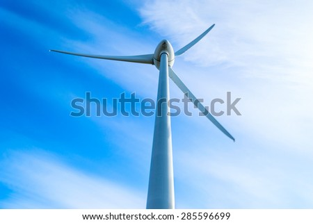 Wind turbine with fine blue sky and white clouds in background. Slight movement visible on blades. - stock photo