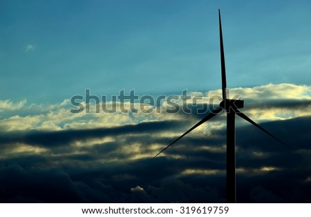 Wind turbine with low clouds background and blue sky at dawn - stock photo