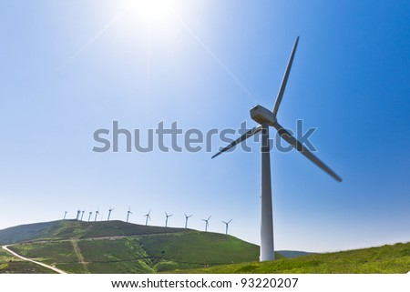 Wind turbine with more behind, horizontal, blade slightly motion blurred - stock photo