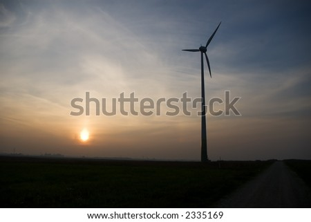 wind turbine with road nearby on sunset