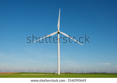 wind turbine with rotation effect on blue sky backround - stock photo