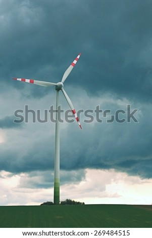 Wind turbine with storm clouds - stock photo