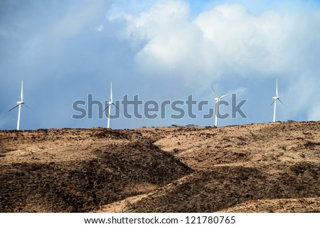 Wind turbines above the coastline in Maui, Hawaii - stock photo