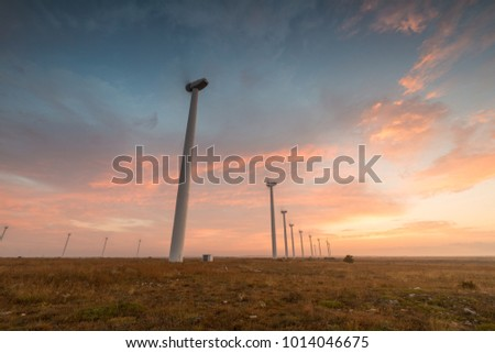 Wind turbines against red, blue and orange sunrise