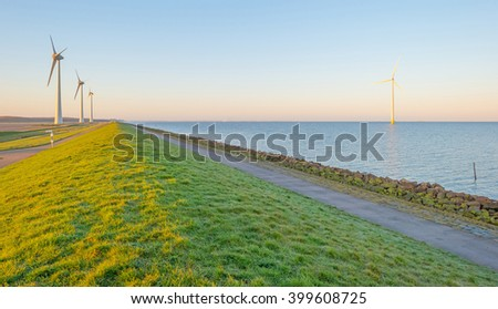 Wind turbines along a dike at sunrise - stock photo