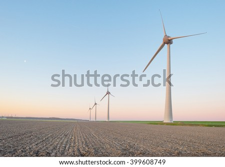 Wind turbines along a dike at sunrise