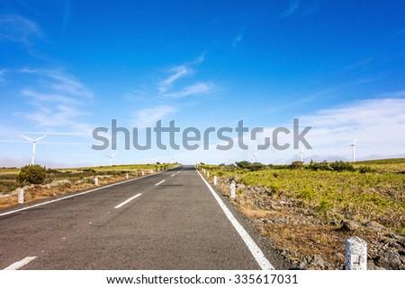 wind turbines along road - natural landscape - stock photo