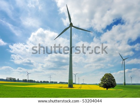 Wind turbines among rapeseed field and green meadows against a dramatically overcast sky - stock photo