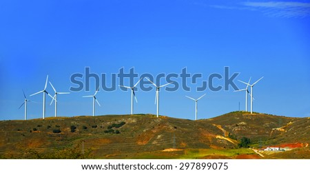 Wind turbines and power lines and poles on the hill in front of blue sky at summer sunny weather - stock photo