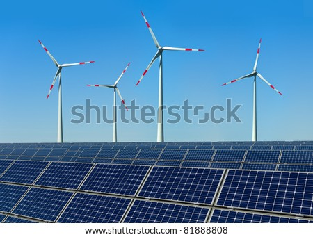 Wind turbines and solar panels against a blue sky - stock photo