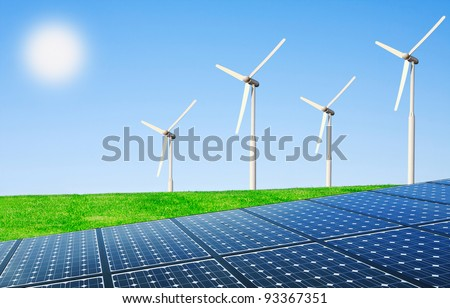 Wind turbines and solar panels in field - stock photo