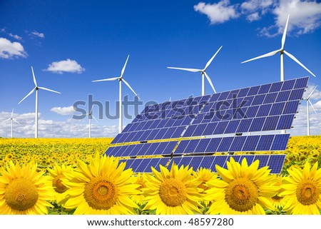 Wind turbines and solar panels on sunflowers field - stock photo