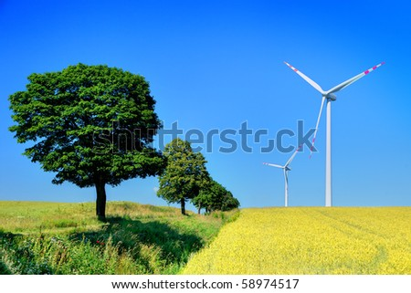 wind turbines and trees, cloudless sky in background - stock photo