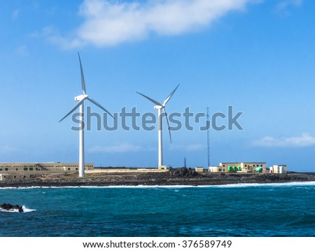 Wind turbines at a sea water osmosis production site, seafront Canary Islands. - stock photo